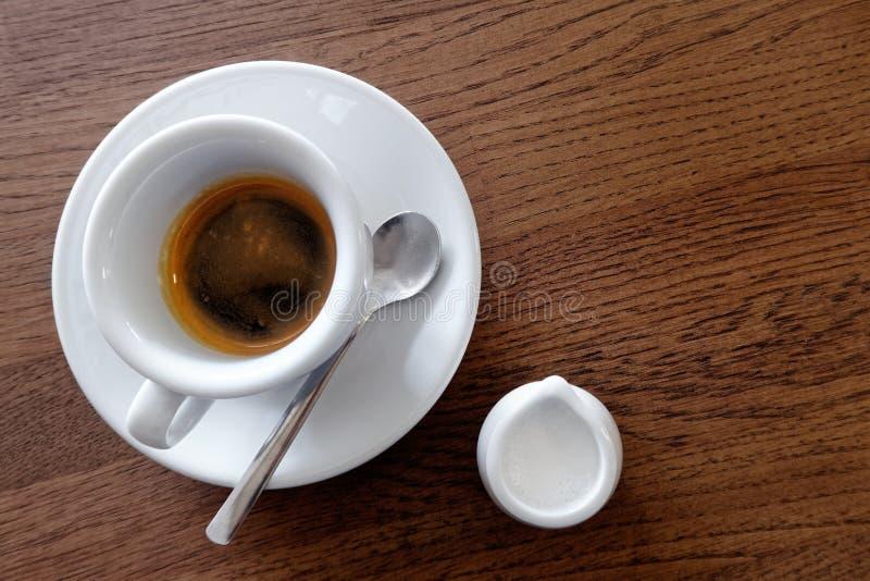 Expresso simple italien classique dans la tasse blanche à côté d'une cruche de lait image stock