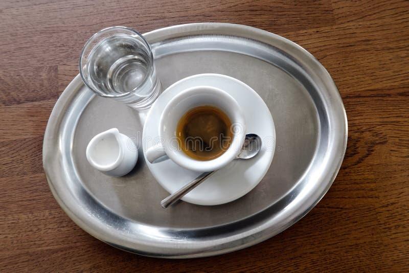 Expresso simple italien classique dans la tasse blanche, une cruche de lait et le wat images stock