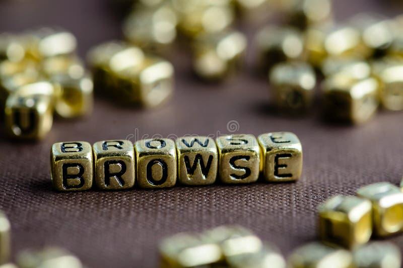 Exprima BROWSE feita das letras douradas pequenas no backgrou marrom fotos de stock