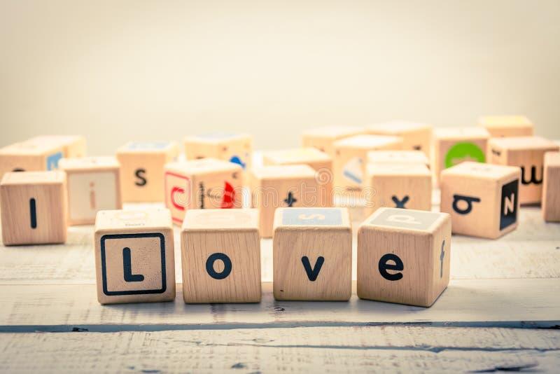 Exprima cúbico de madeira do ` do amor do ` na madeira fotografia de stock
