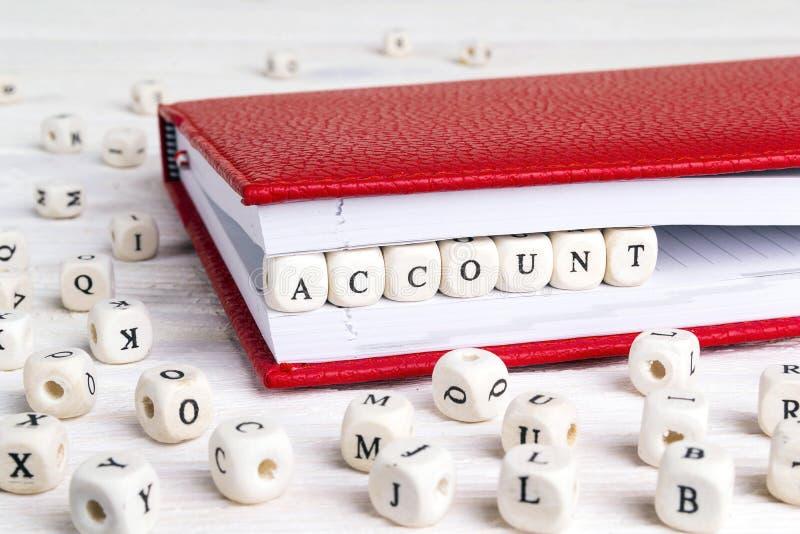 Exprima a conta escrita em blocos de madeira no caderno vermelho em w branco foto de stock royalty free