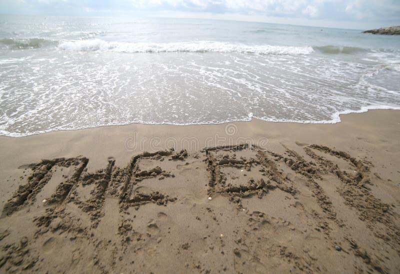 exprima A EXTREMIDADE escrita na areia e na onda que está suprimindo de t fotos de stock royalty free
