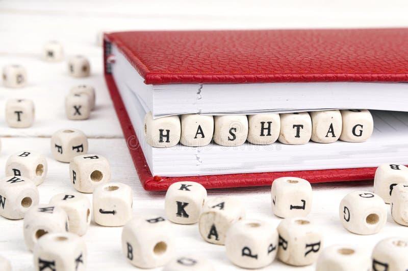 Exprima Hashtag escrito em blocos de madeira no caderno vermelho na tabela de madeira branca foto de stock