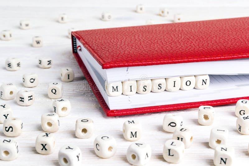 Exprima a missão escrita em blocos de madeira no caderno vermelho em w branco imagens de stock royalty free