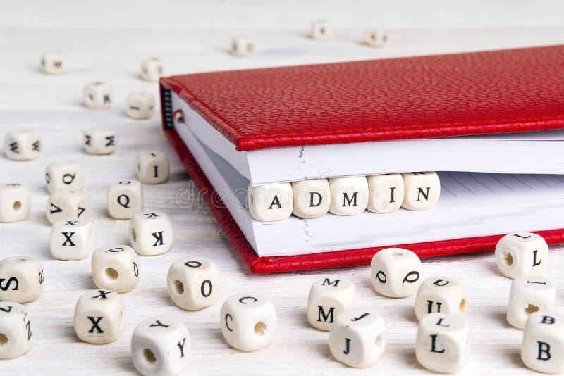 Exprima o Admin escrito em blocos de madeira no caderno vermelho no branco cortejam fotografia de stock