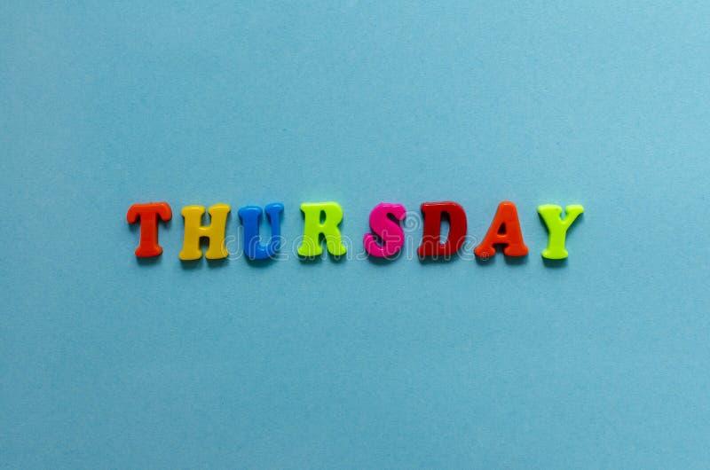 Exprima o ` de quinta-feira do ` da letra magnética plástica colorida no fundo do papel azul fotografia de stock royalty free