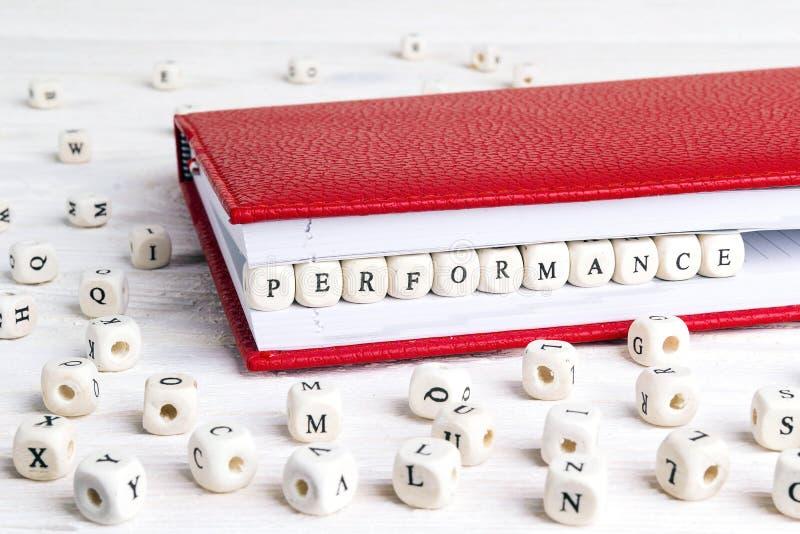 Exprima o desempenho escrito em blocos de madeira no caderno vermelho no whi imagem de stock