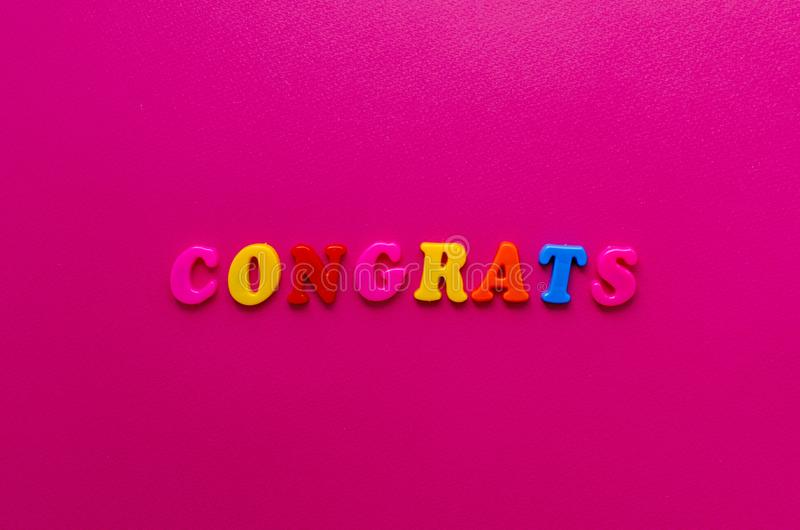 Exprima o ` dos congrats do ` das letras magnéticas no fundo de papel cor-de-rosa fotografia de stock