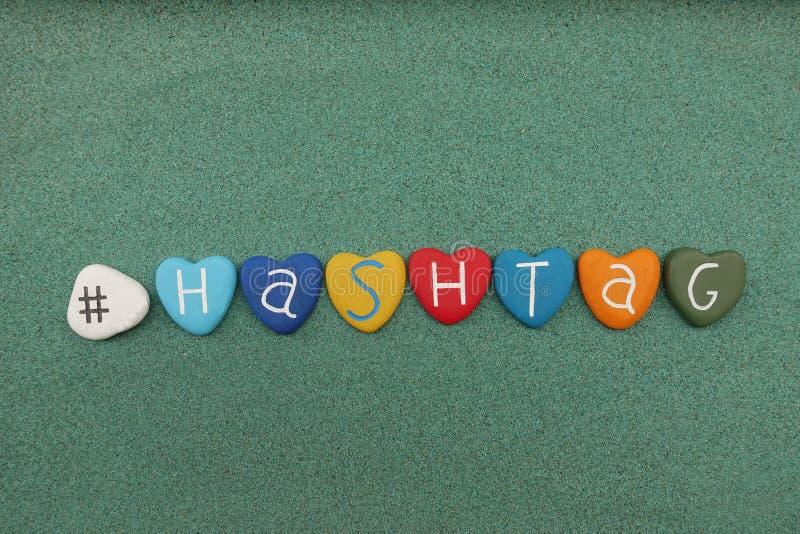Exprima o hashtag composto com as pedras coloridos do coração sobre a areia verde fotos de stock
