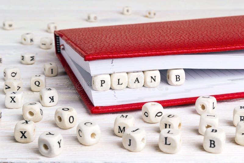 Exprima o plano B escrito em blocos de madeira no caderno vermelho no wo branco imagem de stock