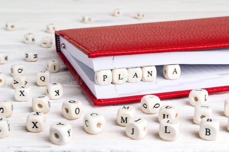 Exprima o plano A escrito em blocos de madeira no caderno vermelho na tabela de madeira branca fotos de stock royalty free