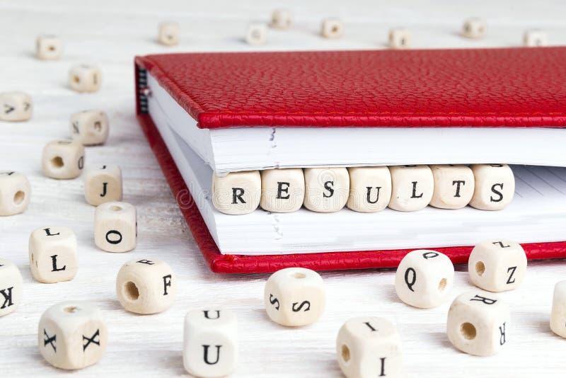 Exprima os resultados escritos em blocos de madeira no caderno vermelho em w branco fotos de stock
