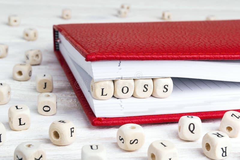 Exprima a perda escrita em blocos de madeira no caderno vermelho na madeira branca fotografia de stock royalty free