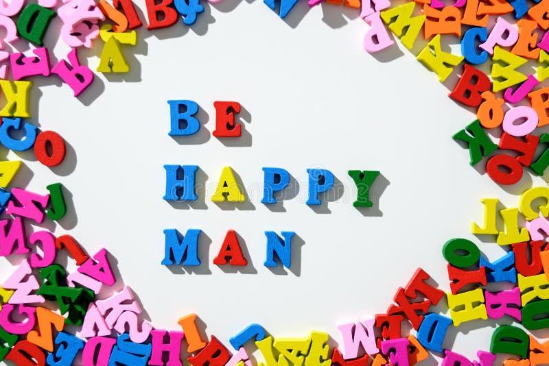 Exprima seja homem feliz alinhado com letras de madeira coloridas em uma tabela branca com dispersado em um círculo com letras imagens de stock royalty free