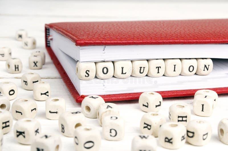 Exprima a solução escrita em blocos de madeira no caderno vermelho no branco foto de stock