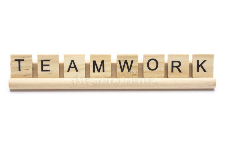 Exprima `` trabalhos de equipa `` escarafuncham sobre letras de madeira em uma cremalheira fotografia de stock