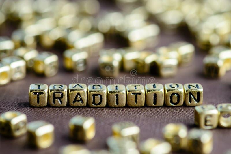 Exprima a TRADIÇÃO feita das letras douradas pequenas no backg marrom fotos de stock royalty free