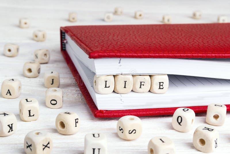 Exprima a vida escrita em blocos de madeira no caderno vermelho na madeira branca imagens de stock royalty free