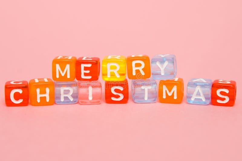 exprime le Joyeux Noël fait de blocs colorés sur le fond rose Configuration plate, vue supérieure - vacances, hiver, Noël et ce d photos stock