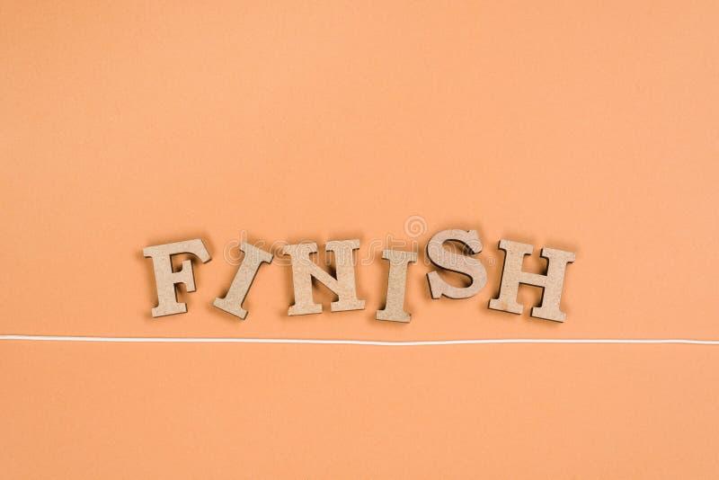 Exprimez la finition avec les lettres en bois et la ligne d'arrivée sur un fond orange photo stock