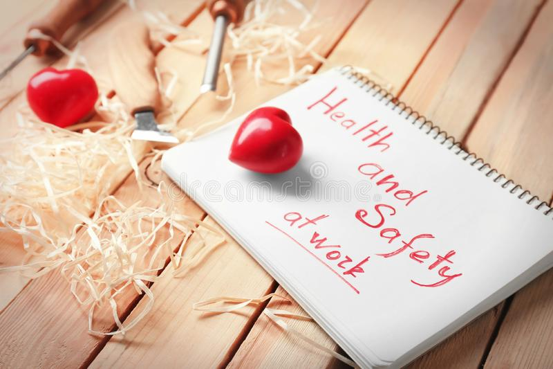 Exprimez la santé et sécurité au travail écrit au carnet, aux outils et aux coeurs rouges sur le fond en bois image stock
