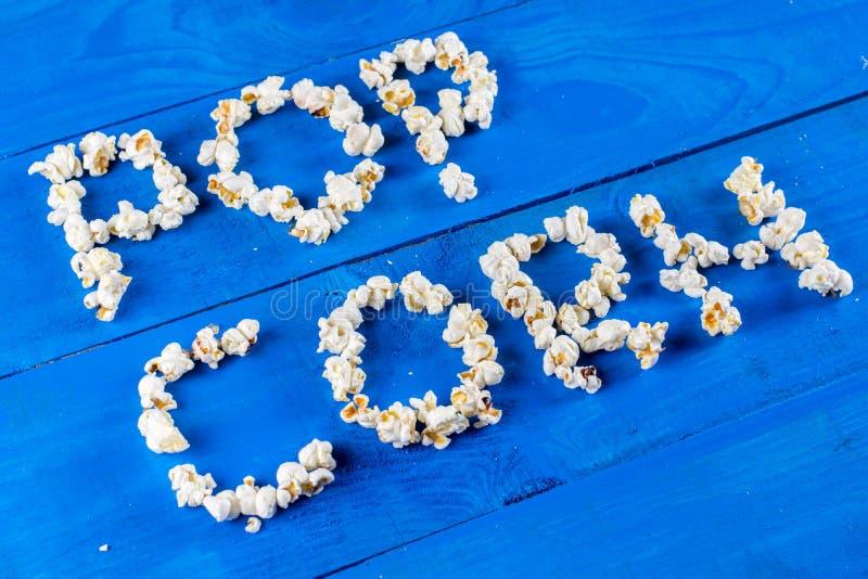 Exprimez le maïs éclaté écrit avec des grains de bruit au-dessus de configuration en bois bleue d'appartement de fond image stock