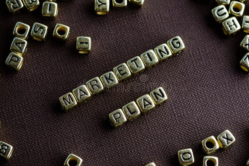 Exprimez le PLAN MARKETING fait à partir de petites lettres d'or sur le brun images stock