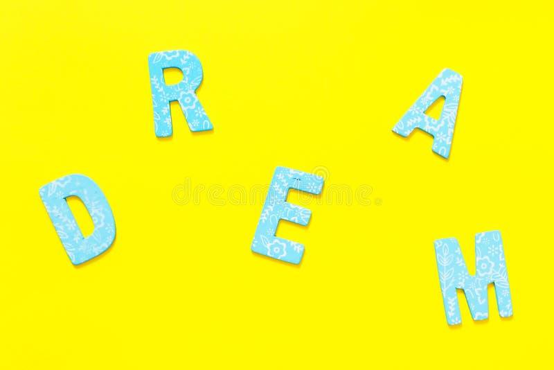 Exprimez le RÊVE fait en petite lettre en bois bleue sur le backgr jaune photo stock