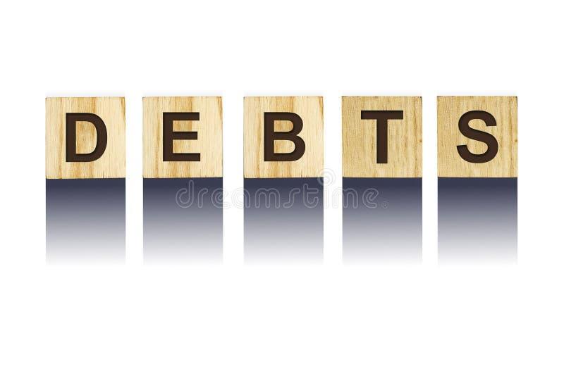 Exprimez les dettes, composées de lettres sur les cubes en bois en construction Fond blanc, affaires d'isolement de concept, fina image libre de droits