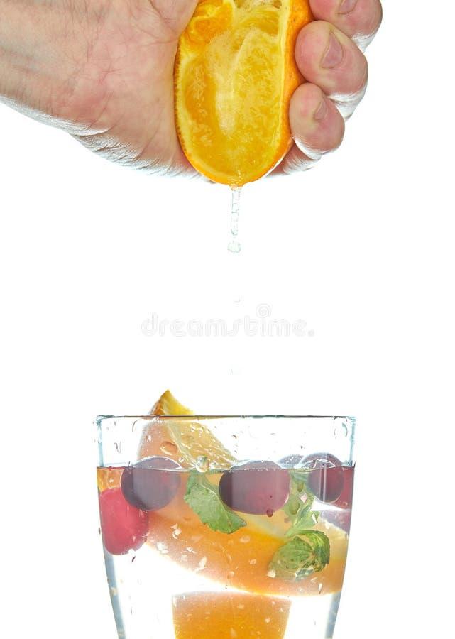 Exprimiendo el zumo de naranja que vierte en un vidrio aislado en blanco agua con el zumo de naranja Bebida de restauraci?n fotos de archivo libres de regalías