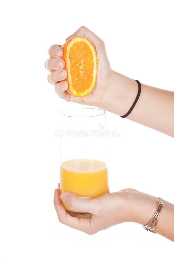 Exprimir la naranja en el vidrio imagen de archivo