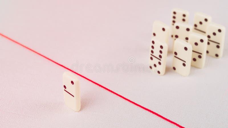 Expulsé du groupe, incapable de croiser la ligne rouge qui les sépare Scène avec le groupe de domino Concept de photo stock