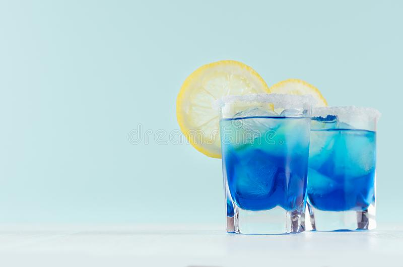Exquisite blue cocktails for celebration in beach style with blue curacao, ice cube, sugar rim, lemon slice in mint color bar. stock photography