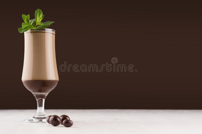 Exquisite chocolate layers dessert with fresh green mint and with round chocolates in dark brown interior, copy space. royalty free stock images
