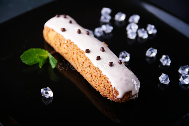 Exquisite cream dessert eclair with fresh mint leaves royalty free stock photography