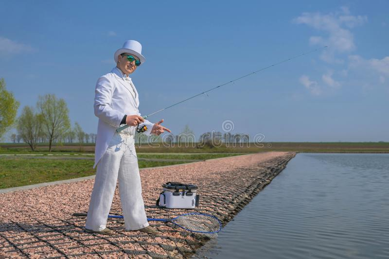 Exquisite fishing. Fisherman in white suit catch fish by spinning rod at trout area lake royalty free stock photo