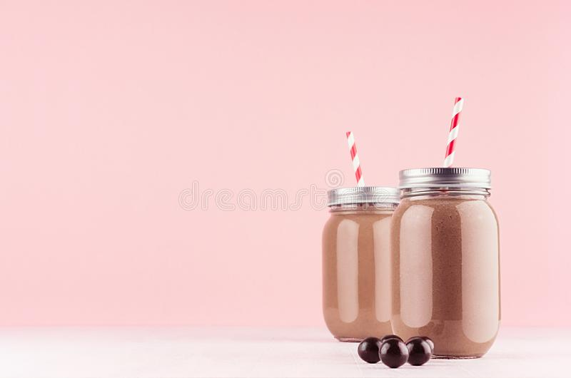 Exquisite light milk chocolate dessert in jars with chocolate balls, red straw, silver cap on modern elegant pink color background.  stock image