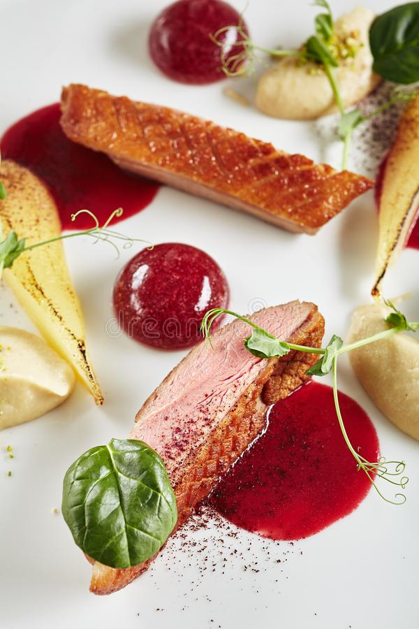 Exquisite Serving Creative Molecular Dish of Duck Breast, Baked Pear and Cherry Spheres royalty free stock photo