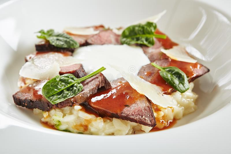 Exquisite Serving White Restaurant Plate of Risotto with Pecorino Cheese and Warm Roast Beef stock images
