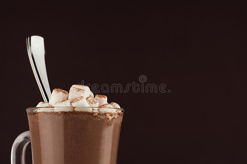 Exquisite sweet hot chocolate drink with marshmallows and silver spoon closeup, top section, detail on dark brown background. Exquisite sweet hot chocolate stock photography