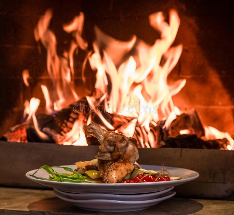 Exquisitely served chicken with vegetables on the background of the fire. royalty free stock photos
