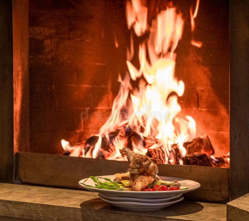Exquisitely served chicken with vegetables on the background of the fire. stock photo