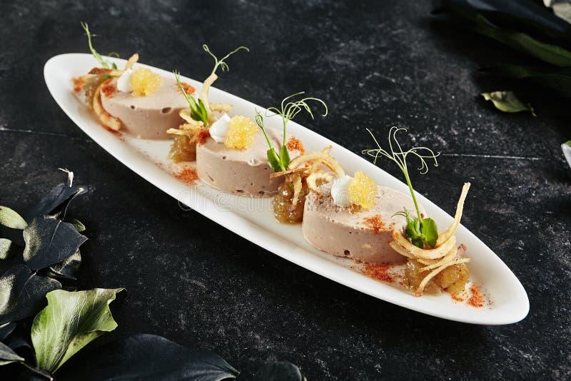 Exquisito restaurante blanco con mousse de hígado de bacalao, cebolla y chuletas crispadas fotografía de archivo libre de regalías