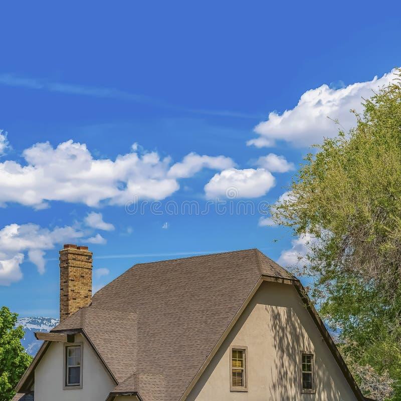 Extérieur carré d'une maison avec les fenêtres brillantes et la cheminée de toit foncé de mur de briques photo libre de droits