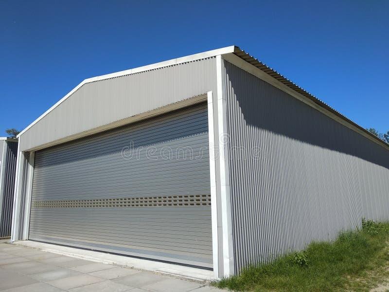 Extérieur d'un hangar en métal pour la fabrication ou le stockage Garage de vue de côté avec les portes de roulement fermées avec photo libre de droits