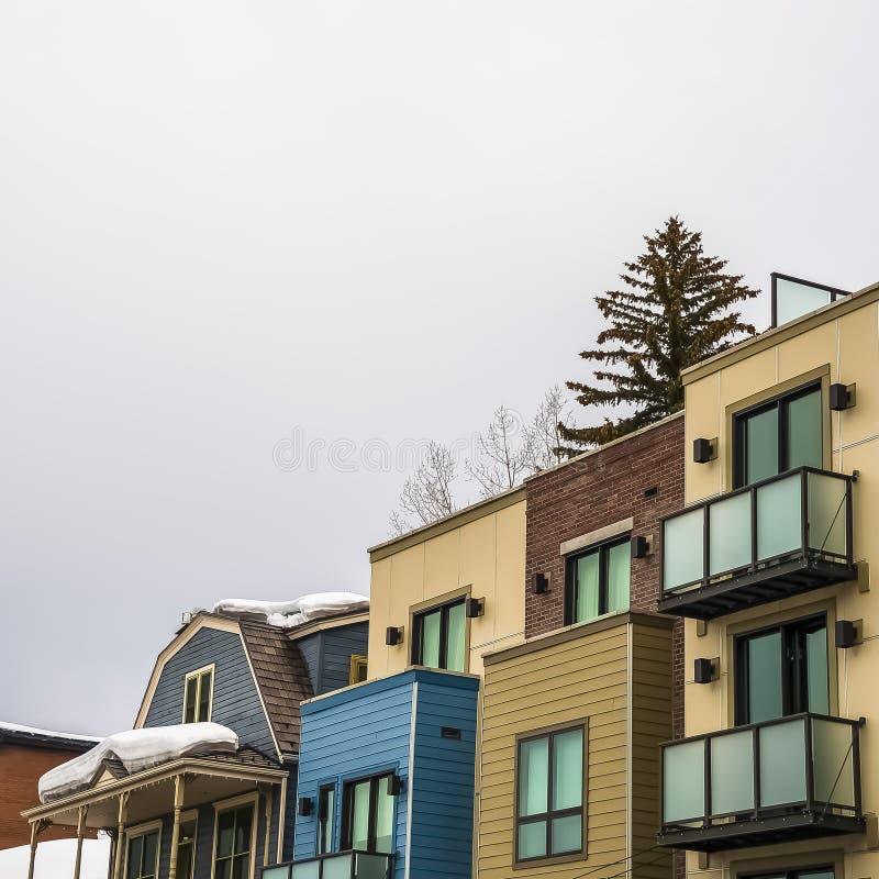 Extérieur de bâtiments résidentiels de place avec les toits neigeux contre le ciel nuageux en hiver image libre de droits