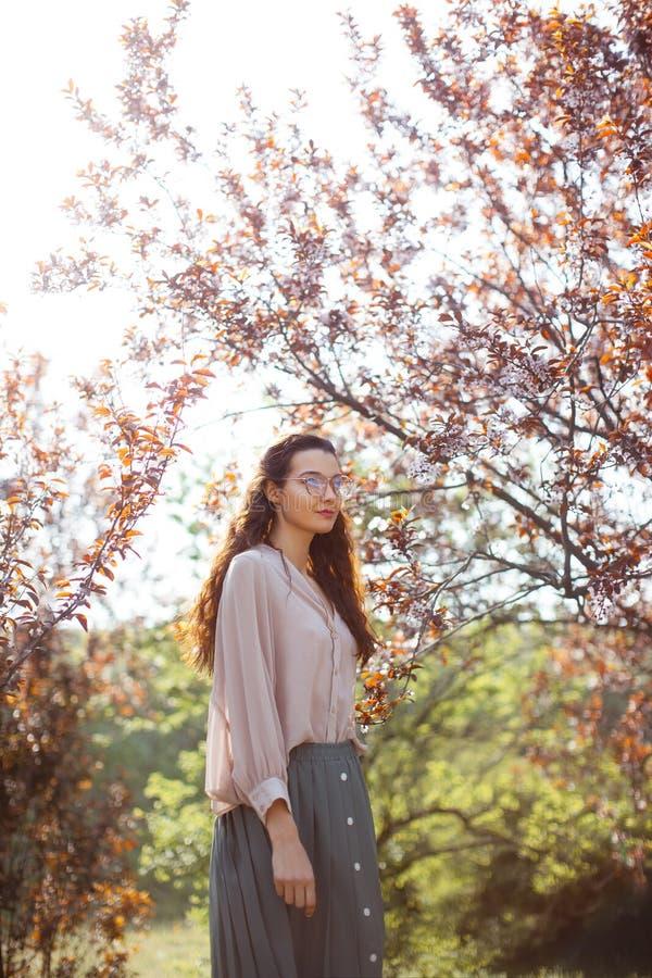 Extérieur de femme en parc près d'arbre de fleur de ressort images stock