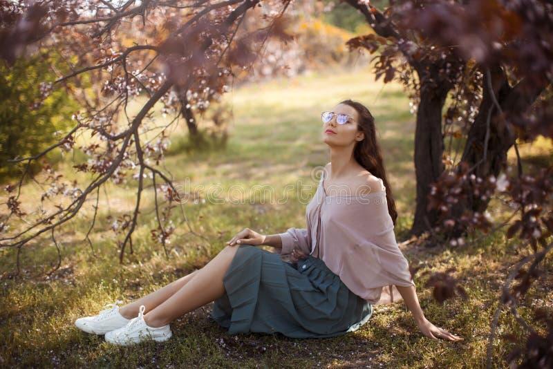 Extérieur de femme en parc près d'arbre de fleur de ressort image libre de droits