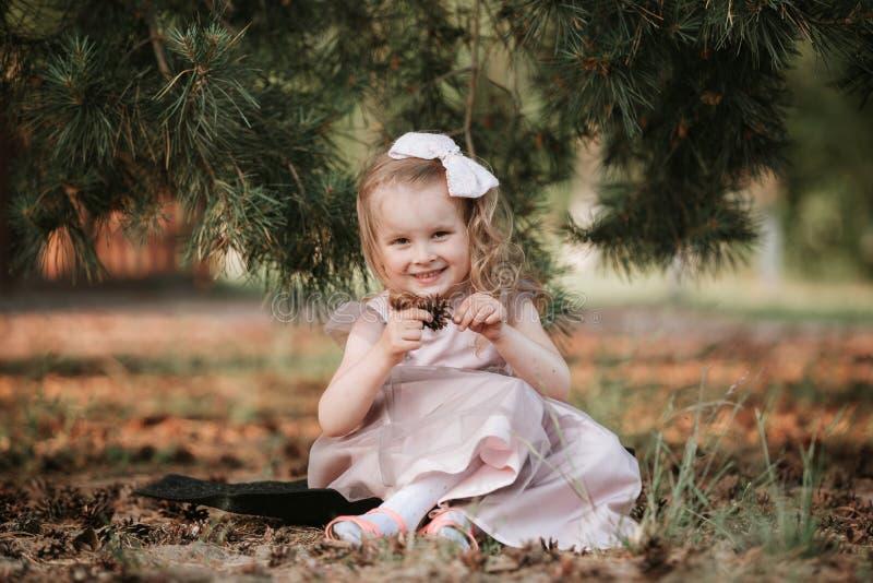 Extérieur de fille de portrait Petite fille stupéfiante dans une pose drôle de robe sur le fond de nature photo libre de droits