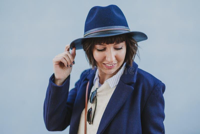 Extérieur de portrait d'une jeune belle femme avec les vêtements élégants posant avec un chapeau moderne lifestyle photographie stock